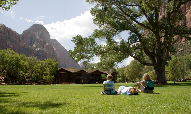 Family getting some rest in front of the Zion Lodge